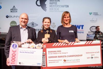 Herzlichen Glückwunsch! Dr. Frank Neuhausen (BWT water+more, l.) und Melanie Hansmeier (Deutscher Kaffeeverband, r.) gratulieren der deutschen Barista-Meisterin 2016 Chloe Natrass (Mitte) zu ihrem Sieg.  /Foto: Sinan Muslu