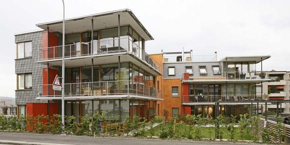 Große Südfenster, leuchtend orange Putzflächen und grüne Schiefer an Dach und Wand prägen das Mehrfamilienhaus in Thalwil