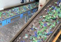 Im Recyclingwerk werden die PET-Ballen aufgebrochen und die Vorsortierung trennt Fremdstoffe vom PET. Die einzelnen Flaschen werden nach Farben sortiert und gewaschen / Quelle: Mitteldeutsche Erfrischungsgetränke GmbH & Co. KG