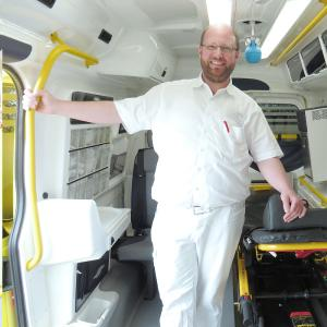 ICW-Wundexperte Mirko Mau steht im Innenraum des Wundmobils und versorgt hier die Wunden von Patienten.