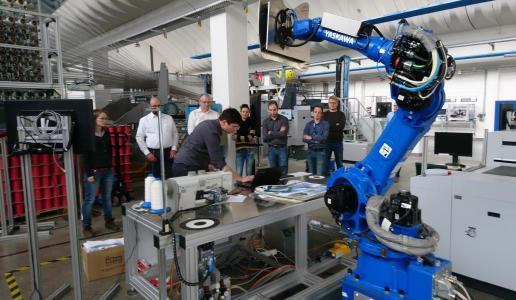 In der Labtour wird eine robotergestützte Bandeinfassung in Kombination mit einem Kamerasystem zur Arbeitssicherheit gezeigt. Foto: STFI