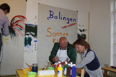 Landrat Günther-Martin Pauli und Oberbürgermeister Helmut Reitemann testen mit Leiterin Karina Matthes die Malwand im Sonnenkinderland