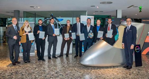 """v.l.n.r.: Jens-Jürgen Härtel (stellv. FSK-Vorsitzender, Volkswagen AG) mit den Preisträgern des FSK Innovationspreises Polyurethane 2015: Mara Freigang (FH Mainz), Peter Schneider (IKV Aachen), Armin Nöthe (BASF), Dr. Frank Prissok (BASF), Sascha Mattfeld (BASF), Thomas Michaelis (Covestro), Stefan Bichler (Adidas), Dr. Hubert Ehbing (Covestro) und Albrecht Manderscheid (FSK-Vorsitzender, CANNON Deutschland) vor der Polyurethan-Hartschaumkabine des """"Solar Impulse"""". Im Hintergrund: das Hochrad """"1865 E-Veloziped"""" von BASF"""