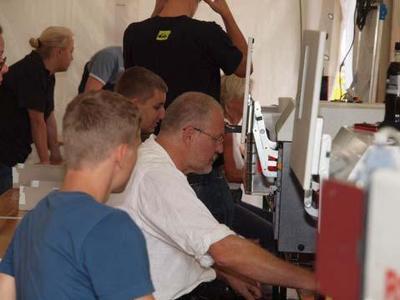 Klaus Huber weist seine Mitarbeiter am Laserbeschrifter ein