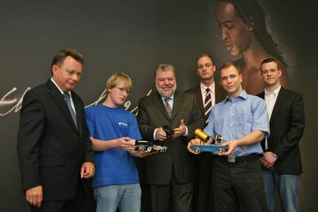 Pressefoto: Ministerpräsident Kurt Beck (mitte), zusammen mit Dr. Josef Staub (links) und vier Auszubildenden zu Besuch bei Schneider-Kreuznach in Bad Kreuznach