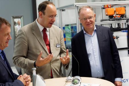 Mobilität mit Brennstoffzelle, dargestellt im Miniaturformat: Klaus Hamacher (li.) und Stephan Weil (re.) erfahren am ferngesteuerten Modell das Funktionsprinzip des Wasserstoff-Antriebs