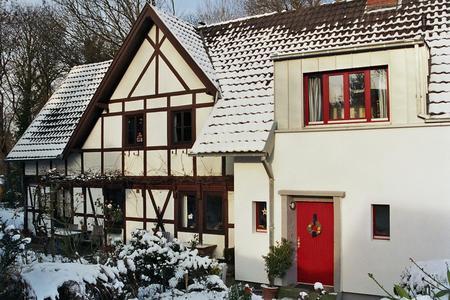 Attraktive Optik: Die roten Echtholz-Fensterrahmen und der grau verputzte Kubus stehen in reizvollem Kontrast zur schneeweißen Front des Altbaus. (Foto: Achim Zielke für INTHERMO)