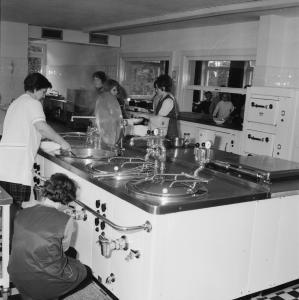 Einblick in die Großküche von damals – im Hintergrund stehen die Schülerinnen und Schüler vor der Essensausgabe an
