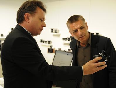 Bildunterschrift: Dr. Josef Staub (li), Geschäftsführer der Jos. Schneider Optischen Werke GmbH, überreicht dem Fotografen Andreas Gursky (re) das 15 Millionste Objektiv.