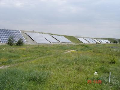 Solarzellen zum Einfangen der Sonnenenergie, säumen den aufgeschütteten Rand des Wärmespeichers.